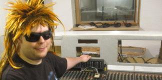 Hymyilevä mies aurinkolaisessa äänityspöydän ääressä
