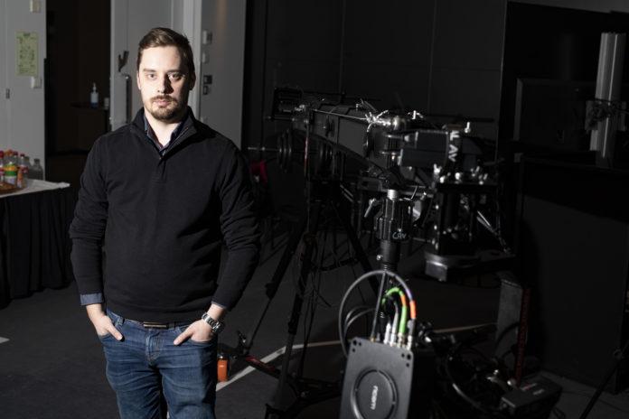 Miika Granholm seisoo kameran vieressä ja katsoo kameraan